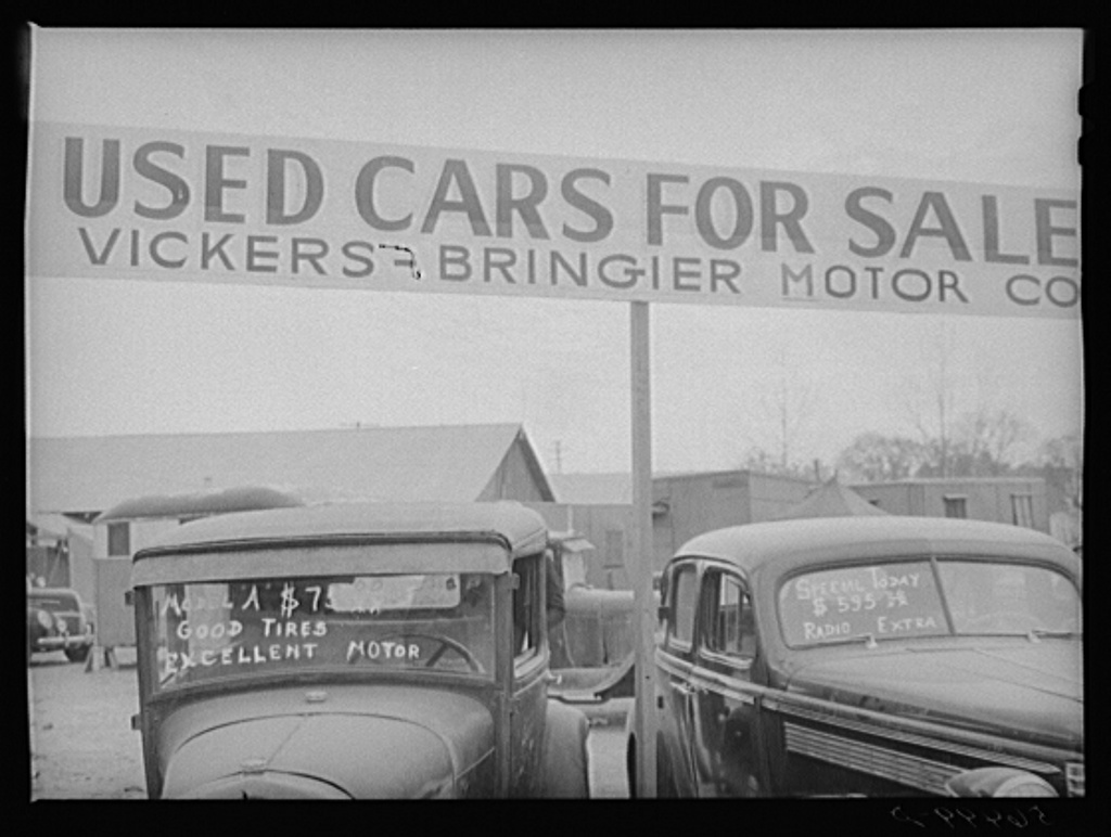 Service station, used cars for sale. Trailers are parked very congested in section near road show and carnival. Alexandria, Louisiana