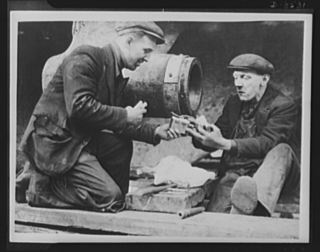 Ship repairers at Surrey Docks, England, making sandwiches for their lunch from American canned meat