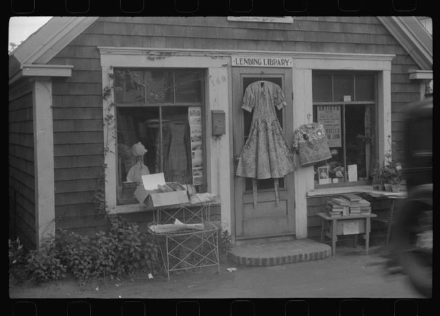 "Shop front. Note dress on door which is ""Provincetown dress,"" local specialty much favored by tourists, almost never worn by Provincetowners. Provincetown, Massachusetts"