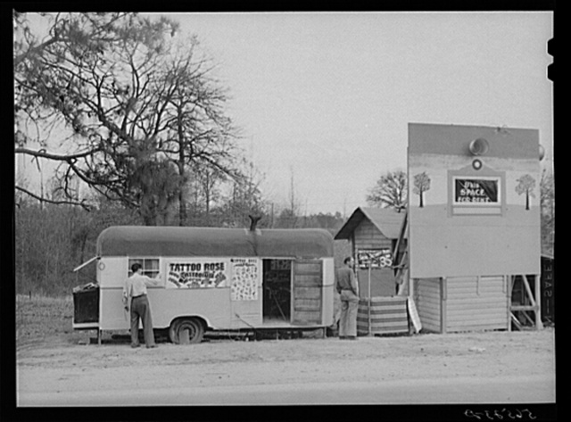 Signs and trailer with tattoo artist on highway near Fort Beauregard.  Alexandria, Louisiana