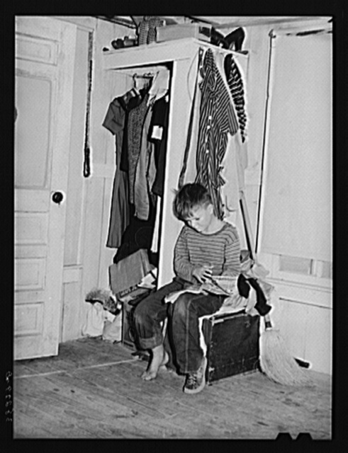 Small boy, son of carpenter from Hobbs, New Mexico, reading funny papers in corner of room in tourist court. Lack of adequate closet space is evident. Corpus Christi, Texas