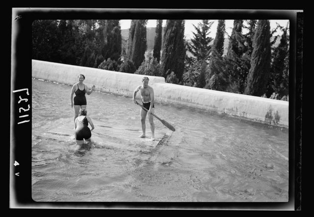 Solomon's pools becomes a picnic & swimming resort. Group of bathers in upper pool, enjoying a raft