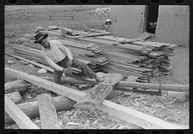 Son of Spanish-American farmer sawing slabs of wood to size for use in roof construction, Amalia, New Mexico