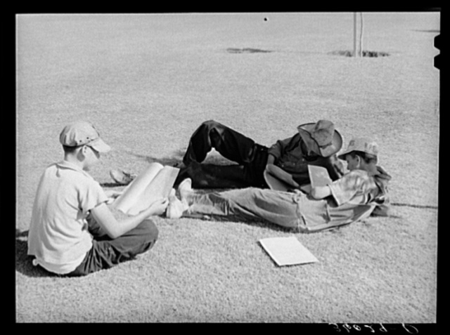 Sons of agricultural workers reading the camp newspaper at the Agua Fria migratory labor camp. Arizona