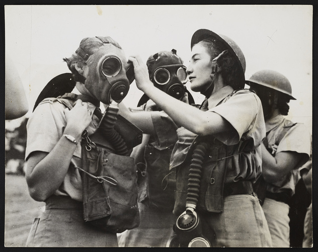 South African women's services on duty in the Middle East: A South African W.A.A.F. Sergeant instructor fitting a gas mask to a beginner