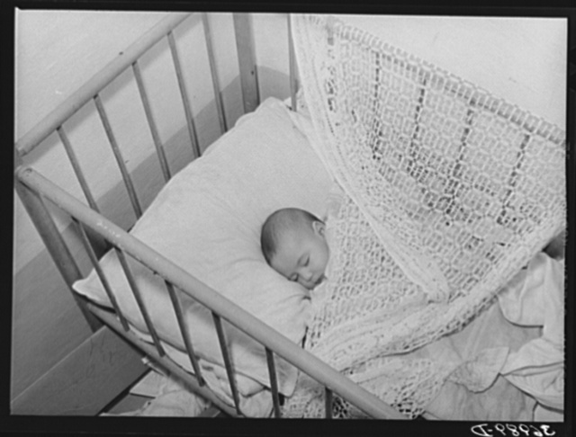Spanish-American baby in its crib. Chamisal, New Mexico