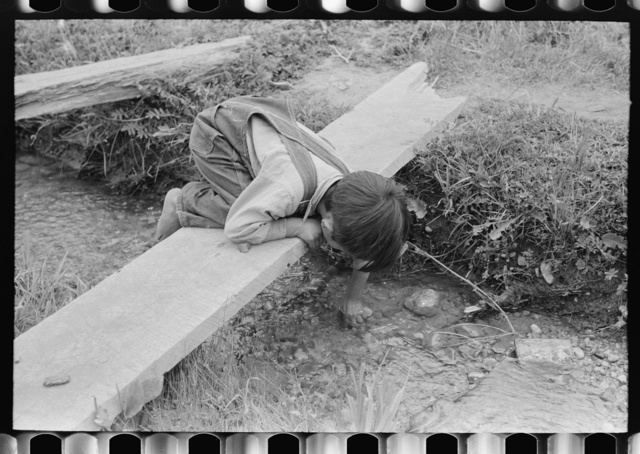 Spanish-American boy playing in irrigation ditch, Chamisal, New Mexico