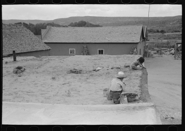 Spanish-American children replastering corner of roof of adobe house, Costilla, New Mexico