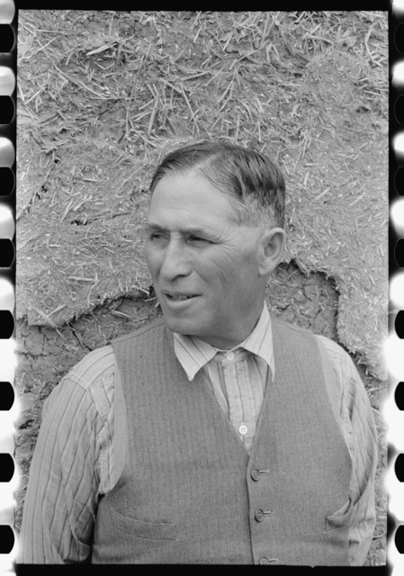 Spanish-American farmer standing in front of adobe wall, Chamisal, New Mexico