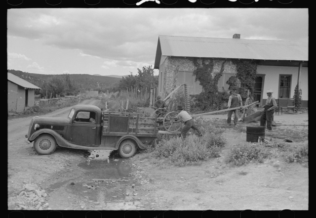 Spanish-American farmers loading a mower onto a track, Chamisal, New Mexico