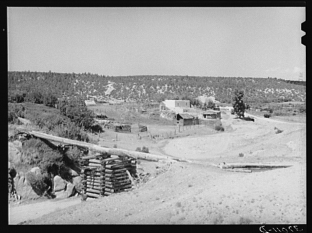 Spanish-American farn near Trampas, New Mexico. Irrigation water crosses ditch in wooden trough