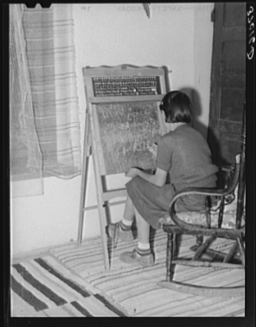 Spanish-American girl who is learning English with the aid of blackboard instruction. Chamisal, New Mexico