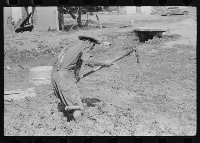 Spanish-American mixing adobe plaster, Chamisal, New Mexico