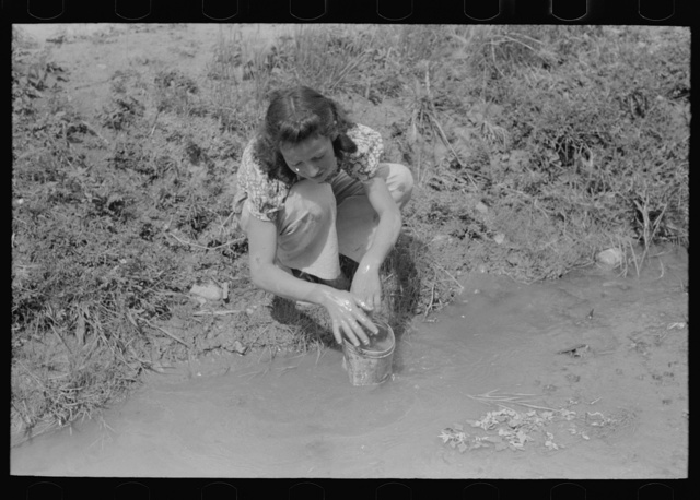 Spanish-American woman washing in irrigation ditch, Chamisal, New Mexico