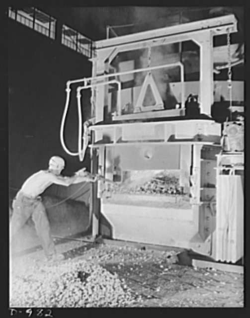 Steel alloy manufacture. Allegheny Ludlum Steel Corporation, Brackenridge, Pennsylvania. Converting scrap iron and steel into high quality alloy steel. A workman adds alloying materials to the bath of molten steel in one of the thirty-five ton electric arc furnaces. These furnaces give faster heating and more accurate temperature control than do open hearth furnaces