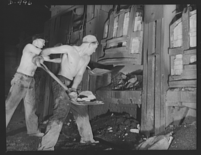 Steel alloy manufacture. Allegheny Ludlum Steel Corporation, Brackenridge, Pennsylvania. Open hearth steel is also made at this plant. Workers here shown are completing the charge to an open hearth furnace which has a capacity of about 100 tons per heat. Only small quantities of materials are charged by hand in this way. The bulk of the material is charged by the mechanism shown in pictures nos. D-995 and D-994