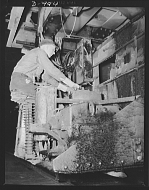 Steel alloy manufacture. Allegheny Ludlum Steel Corporation, Brackenridge, Pennsylvania. Open hearth steel is also made at this plant. Here a worker sits at the controls of the charging mechanism for loading materials and elements into the furnace. This open hearth furnace has a capacity of about 100 tons per heat