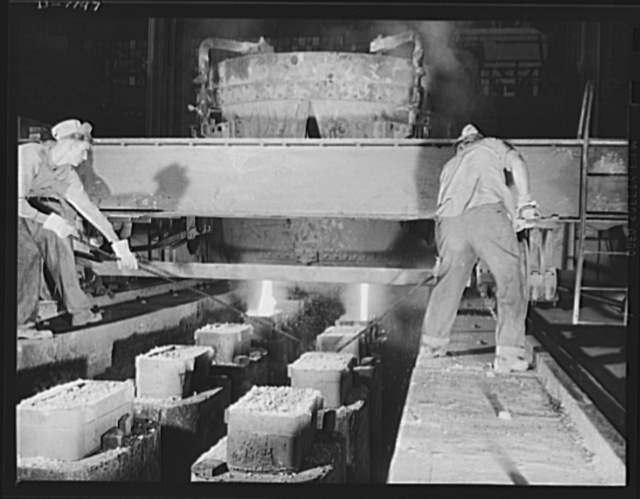 "Steel manufacture, Allegheny-Ludlum. Ladling it out! These workers are casting ingots from the ladle into which a thirty-five ton electric furnace has just poured its molten steel. The ""hot tops"" allow for shrinkage of the steel in the ingots bodies. If these should be any slag left in the molten steel, it will rise into these hot tops, since slag is lighter than the steel"