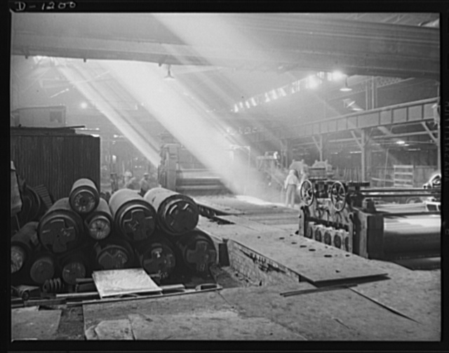 Steel manufacture, Allegheny-Ludlum. Space is a prime requisite for a steel plant. The huge production machinery itself and the various tools for treatment of the steel after it has been refined may extend for acres. In the center here is the exit end of a plate mill. After the plates are hot-rolled and released, they pass through the roller leveling device at the right, where they are flattened for commercial use