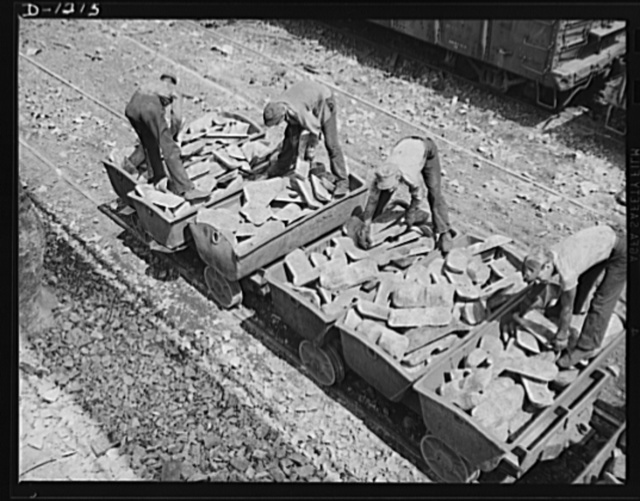 Steel manufacture, Allegheny-Ludlum. This doesn't look very impressive, just a pile of rock. Well, that's what it is, a pile of limestone, but since limestone is the main ingredient for the refining of high quality steels, heaps of rock such as these are mighty important factors in the maintenace of defense production. Here workers are loading the pigs into charging boxes, which will carry them into the open hearth furnace for melting