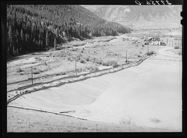 Tailing pit of active gold mine in the valley of the Animas River, San Juan County, Colorado. Ranchers and farmers who want to use water for irrigation in the lower valley have always attempted to force the mine and mill operators to keep the tailings from polluting the streams; however, without much success