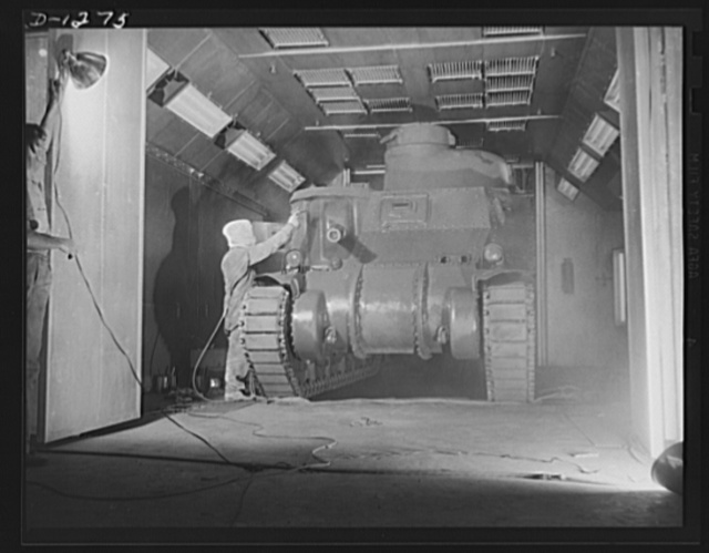 Tank manufacture (Chrysler). The final cost of olive drab paint is applied by spraygun to the twenty-eight ton M-3 tank just before it leaves the huge Chrysler tank arsenal in Detroit