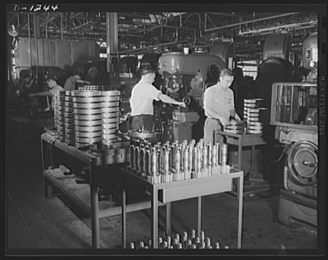 """Tank manufacture (Chrysler). The worker in the foreground is inspecting herringbone gears for Chrysler twenty-eight ton medium tanks, just after they have been finished, or """"shaved."""" All parts of these tanks undergo constant inspection after each of the various operations which eventually result in the complete assembled tank"""