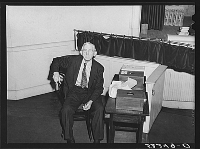 The former sheriff of Woodstock, Vermont, guarding the ballot boxes while he eats his lunch during town meeting noon recess. Woodstock, Vermont
