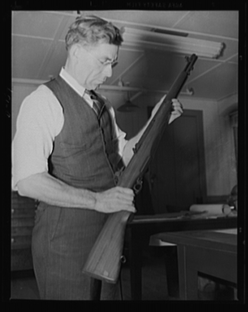 The man behind the gun. John C. Garand, inventor of the semi-automatic rifle now being turned out in large quantities under the war program, looks over one of the guns