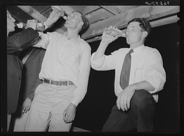The men have a bottle of beer at the square dance. Pie Town, New Mexico