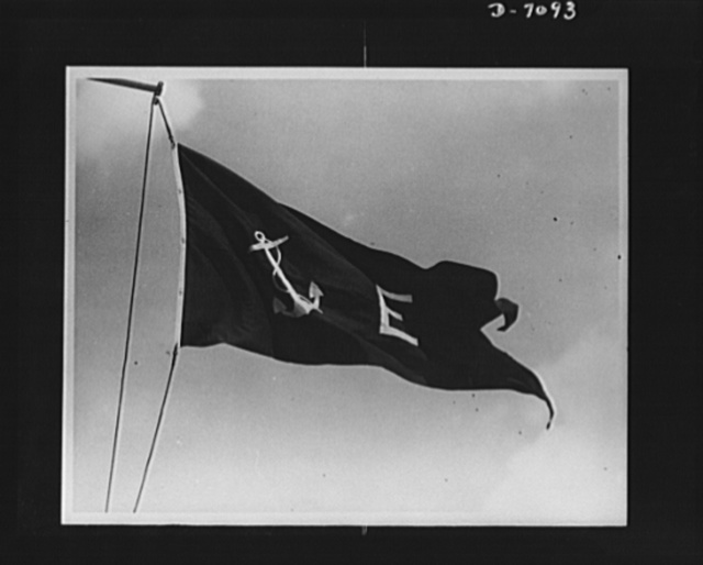 """The new Navy """"E"""" pennant flying from a yardarm in correct Navy manner. If the Stars and Stripes are flown in conjunction with this """"E"""" pennant, the former should be on a seperate hoist and should fly above the burgee. The pennant in this photograph replaces the former Navy """"E"""" pennant. """"E"""" is the traditional Navy symbol of a excellande and has been used on Navy ships for years"""