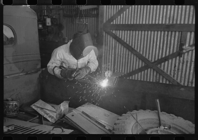 The United Producers and Consumers Cooperative maintains an automobile repair shop. In this picture, a worker is repairing a farmer's truck with an electric welder. Phoenix, Arizona