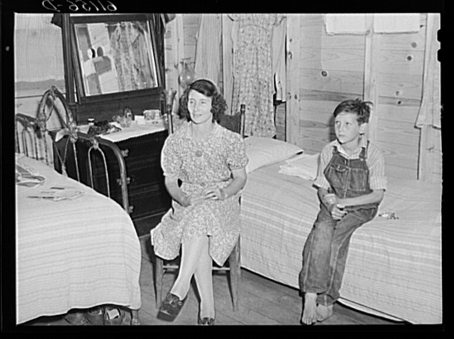 This woman works in the packing plant. Her son works picking fruit with his father. Cabin owned by packing plant rents for one dollar and seventy-five cents a week. Berrien County, Michigan