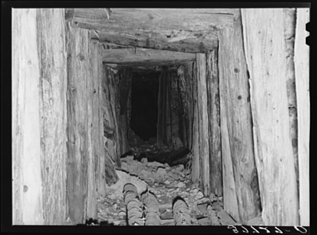 Timbered tunnel leading into mine. San Juan County, Colorado. Barren mountain sides attest to the amounts of timber which was used in construction of such tunnels as this