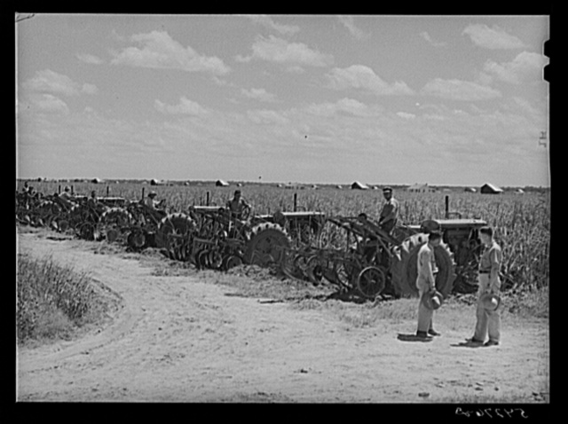 Tractors in the sugarcane fields, with the farm supervisor discussing the problem of cultivation after excessive rains with the foreman, who was chosen from among their own group by the members of the cooperative. Terrebonne Project, Schriever, Louisiana