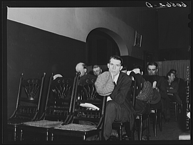 Transient men listening to sermon during evening service at city mission,  Dubuque, Iowa. After the services they fumigate their clothes, take baths and go to bed