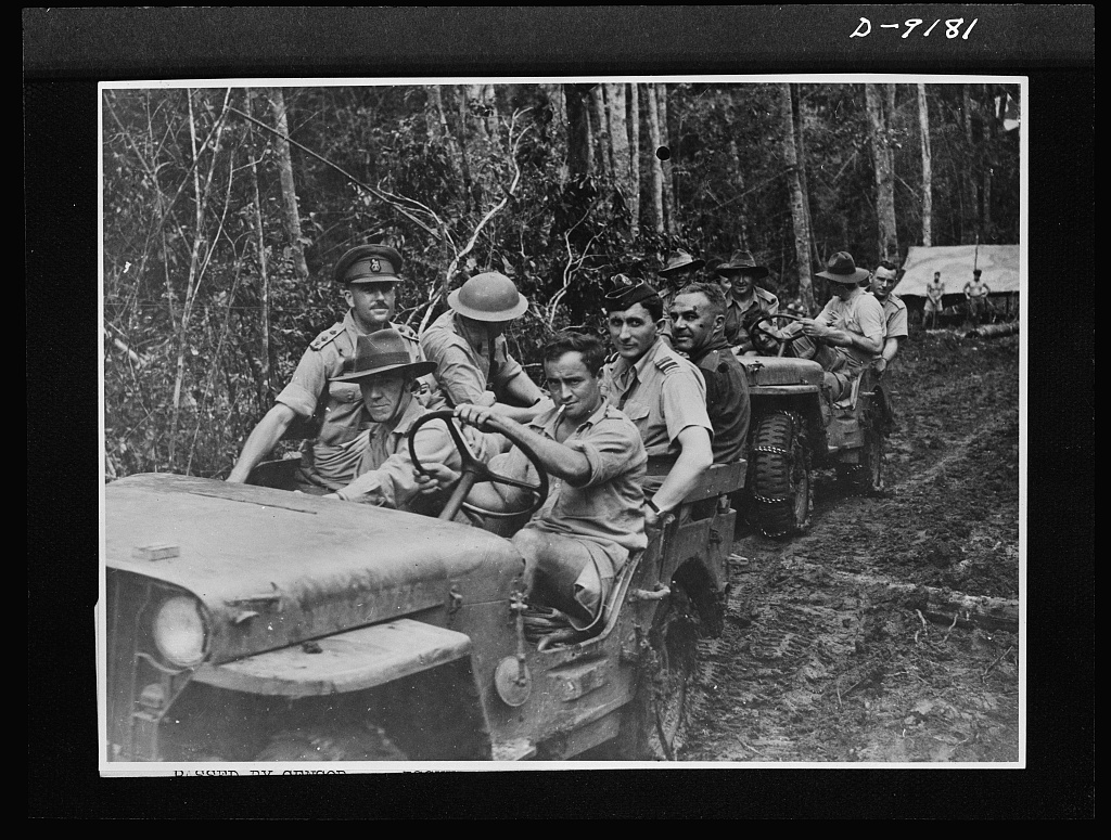 Troops in Australia. American jeeps carried Australian military chiefs and cabinet ministers in a recent visit to battle areas in New Guinea. Air Vice-Marshall G. Jones is shown in the leading vehicle during the tour of the convoy