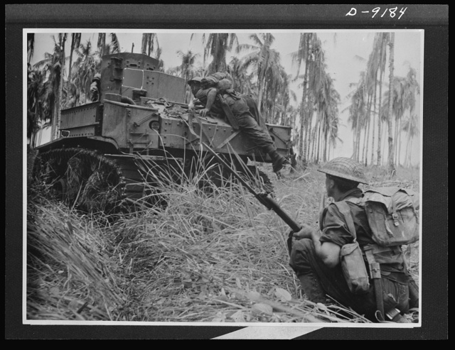 Troops in Australia. An American light tank, manned by an Australian crew, smashed through Japanese pillboxes in the final assault on Buna. This picture, taken during the actual fighting, shows an infantry commander jumping on the tank to warn the crew of a pillbox at the right, which the tank blasts away at another ahead. An infantryman in foreground stands ready to pick off Japs as the pillbox is blasted