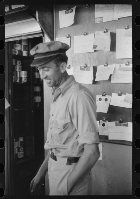 Truck driver in front of bulletin board in a truck service station on U.S. 1 (New York Avenue) in Washington, D.C.