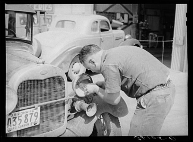 United Producers and Consumers Cooperative repairman replacing light bulb in automobile of member. Phoenix, Arizona