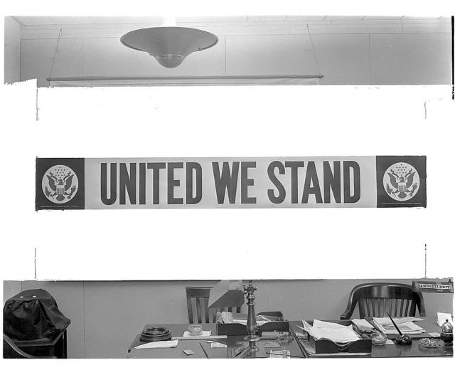 United we stand. Streamer prepared by the Office of Emergency Management (OEM) for use in defense plants throughout the nation. The poster measures 2 X 12 feet. The lettering is red against a white background, with the Great Seal of the U.S. appearing in blue