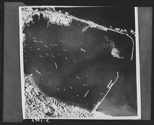 U.S. Air Force bombs Tripoli. U.S. Army bombers made their first raid on Tripoli recently and returned with this unusal series of pictures showing the results of the raid. Their objective was the Spanish mole at upper left and they were not aiming at ships in the harbor. This photo first in the series was taken at the start of the raid