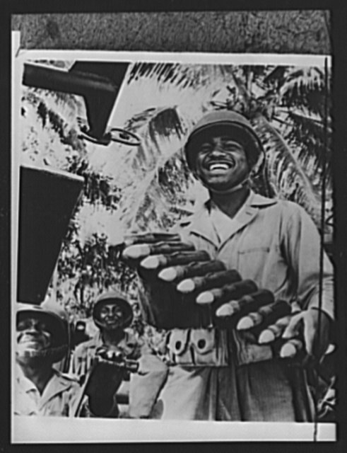 U.S. anti-aircraft gun crew. Corporal Raymond Elliott holds a clip of anti-aircraft shells before loading the weapon of his Negro gun crew at a U.S. Army air base in the New Hebrides in the South Pacific