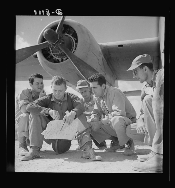 U.S. desert airmen check bombing plans. The crew of an U.S. Army Air Force B-25 bomber check their flight plans at a desert air base before taking off to bomb advance Axis position. They are (left to right) Lieutenant Bob Hill, Clear Lake, Iowa, bombardier; Lieutenant Bill Brytan, Denton, Texas, pilot; Lieutenant Jack Cross, Austin, Texas, navigator (he's checking the time); and Lieutenant Don Castle, Saint Joseph, Missouri, co-pilot; (crew member in rear is unidentified)