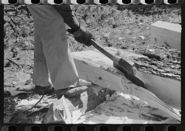 Using a broad axe to remove large chunks from log which will be made into a tie, Pie Town, New Mexico