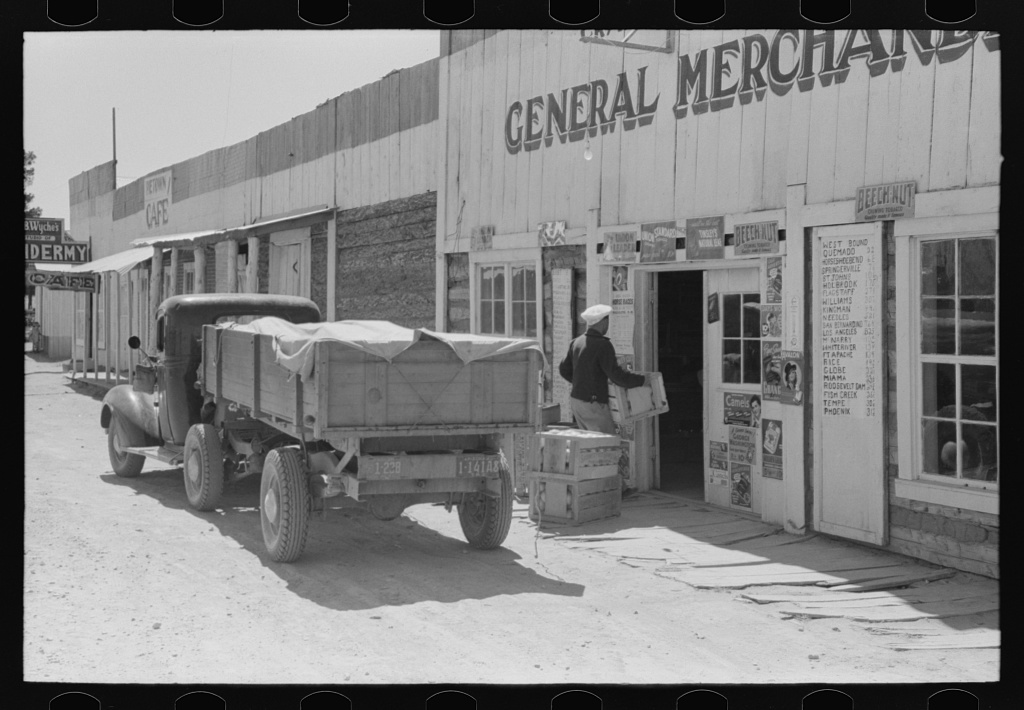 Vegetable and fruit trucker in front of general store, Pie Town, New Mexico. Grapefruit which he brings in is from Arizona