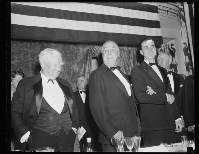 V.P. PENSIVE AS PRESIDENT IS HAPPY OVER RECEPTION AT JACKSON DAY DINNER. WASHINGTON, D.C. JANUARY 8. VICE PRESIDENT GARNER SEEMED PENSIVE IN THIS PICTURE AS PRESIDENT ROOSEVELT ACKNOWLEDGES WITH A SMILE THE TUMULTUOUS GREETING EXTENDED HIM ON ARRIVAL AT THE $100 A PLATE JACKSON DAY DINNER IN WASHINGTON TONIGHT. THE PRESIDENT IS ON THE ARM OF HIS SON, FRANKLIN D., JR.