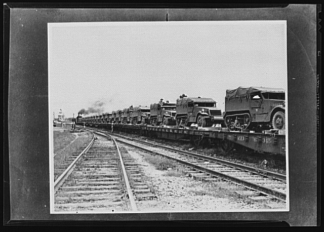 War transportation. Military traffic comes first. One reason why shipments of gasoline and other civilian materials are delayed is because the movement of such army equipment as those half-trac scout cars must have priority over other transportation