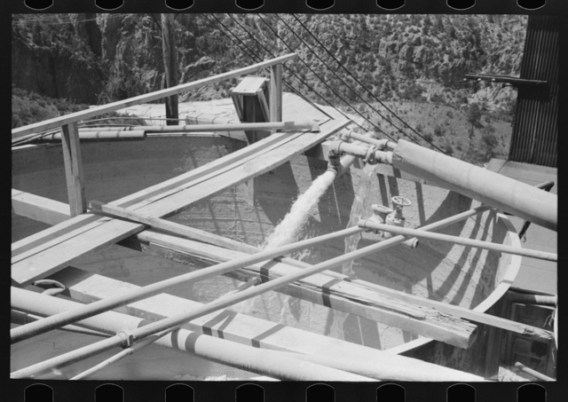 Water being discharged into large mixing vats. Mill at gold mine, Mogollon, New Mexico