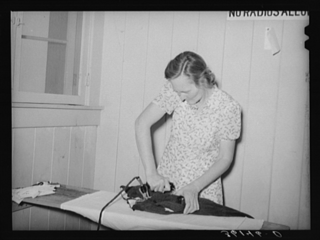 Wife of agricultural worker ironing at the Agua Fria migratory labor camp. Arizona